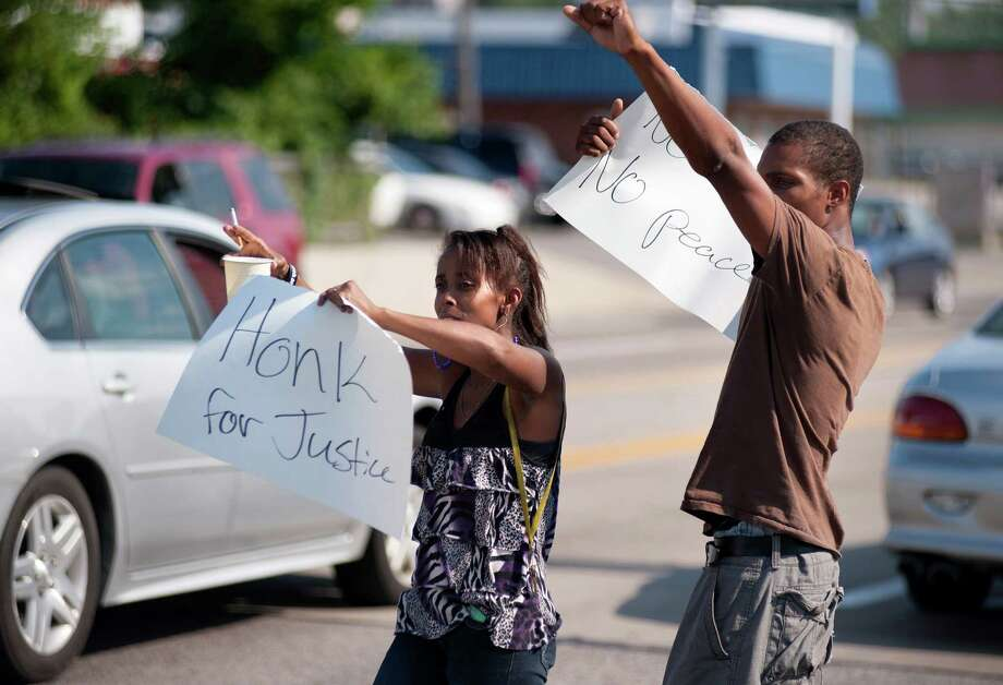 Protesters appeal to motorists for support while rallying on Monday, Aug. 11, 2014 in front of the QT gas station in Ferguson, Mo. that was looted and burned during rioting overnight that followed a candlelight vigil honoring 18-year-old Michael Brown, who was shot Aug. 9, 2014  by Ferguson police officers. Brown, who was killed in a confrontation with police in the St. Louis suburb, was shot Saturday and died following the confrontation with police. Photo: Sid Hastings, AP / SID HASTINGS