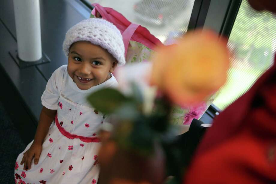 Reina Pena, 4, is all smiles after handing her mother a flower at Texas Children's Hospital on Monday in observance of Tu b'Av, a Jewish day of love that is equivalent to St. Valentine's day. Photo: Mayra Beltran, Staff / © 2014 Houston Chronicle