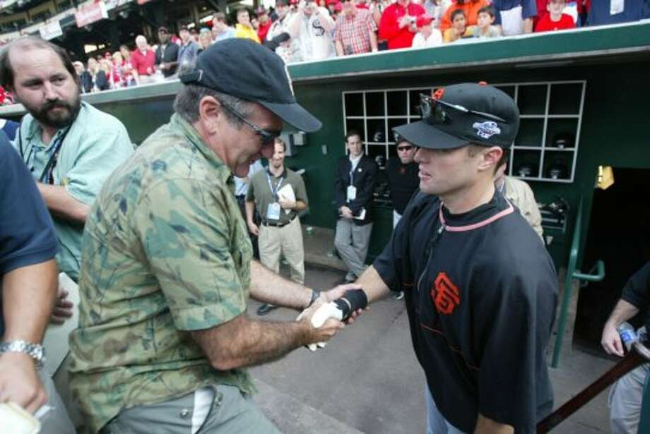 "San Francisco celebrity Robin Williams greets JT Snow in the Giants dugout in 2002. ""Now batboys everywhere are safe thanks to JT Snow,"" said Williams. Photo: Michael Macor, SFC"