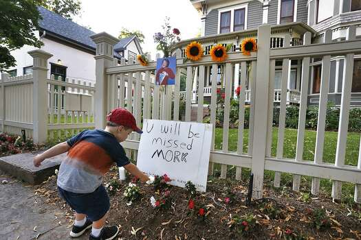 "AJ Polis leaves a flower alongside a placard and a photo of the late actor Robin Williams as Mork from Ork, as people pay their respects at the home where the 80's TV series ""Mork & Mindy"",was set, in Boulder, Colo., Monday Aug. 11, 2014. Williams, the Academy Award winner and comic supernova whose explosions of pop culture riffs and impressions dazzled audiences for decades and made him a gleamy-eyed laureate for the Information Age, died Monday in an apparent suicide. He was 63. Photo: Brennan Linsley, Associated Press"
