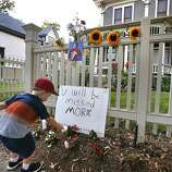 """AJ Polis leaves a flower alongside a placard and a photo of the late actor Robin Williams as Mork from Ork, as people pay their respects at the home where the 80's TV series """"Mork & Mindy"""",was set, in Boulder, Colo., Monday Aug. 11, 2014. Williams, the Academy Award winner and comic supernova whose explosions of pop culture riffs and impressions dazzled audiences for decades and made him a gleamy-eyed laureate for the Information Age, died Monday in an apparent suicide. He was 63."""