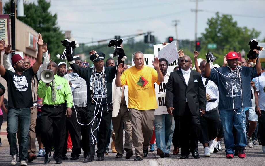 Protesters with arms in the air march on West Florissant Street in Ferguson, Mo., in front of police headquarters on Monday to protest the shooting of Michael Brown by a Ferguson police officer on Saturday. Photo: Sid Hastings, FRE / FR158536 AP