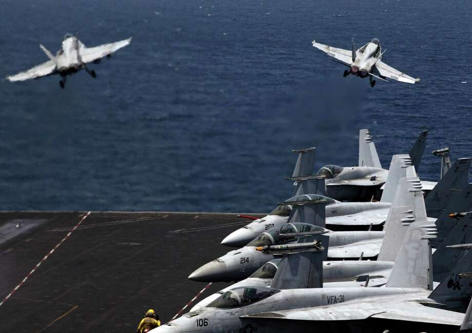 U.S. F/A-18 fighter jets take off for mission in Iraq from the flight deck of the U.S. Navy aircraft carrier USS George H.W. Bush, in the Persian Gulf, Monday, Aug. 11, 2014. U.S. military officials said American fighter aircraft struck and destroyed several vehicles Sunday that were part of an Islamic State group convoy moving to attack Kurdish forces defending the northeastern Iraqi city of Irbil. (AP Photo/Hasan Jamali) Photo: Hasan Jamali, STR / AP