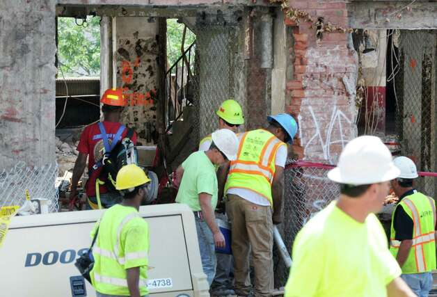 Workers enter the large brick building on Howard St. which is being demolished to make way for Albany's new convention center Monday, Aug. 11, 2014, in Albany, N.Y. (Will Waldron/Times Union) Photo: WW / 00028122A