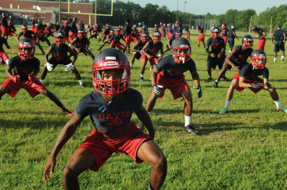 Aldine Davis senior defensive back Markus Allen, front, and his teammates work through their calisthenics on the first day of practice Monday. The pads and hitting will come later for the Falcons. Photo: Jerry Baker, Freelance