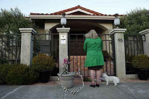 A woman, who did not want to be identified, stands with her pet dog in front of the home of Robin Williams in Tiburon, Calif. on Monday, August 11, 2014. Photo: Scott Strazzante, The Chronicle