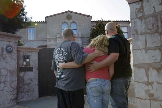 L-R, Brian Duncan, Alexis Cooney, and Nick Cooney, embrace after bringing flowers to Robin Williams' former home in the Sea Cliff neighborhood in San Francisco, Calif., on Monday, August 11, 2014. Williams was found dead in his Tiburon home earlier in the day and fans and friends left  flowers and notes to honor the comedy and acting legend. Photo: Carlos Avila Gonzalez, The Chronicle