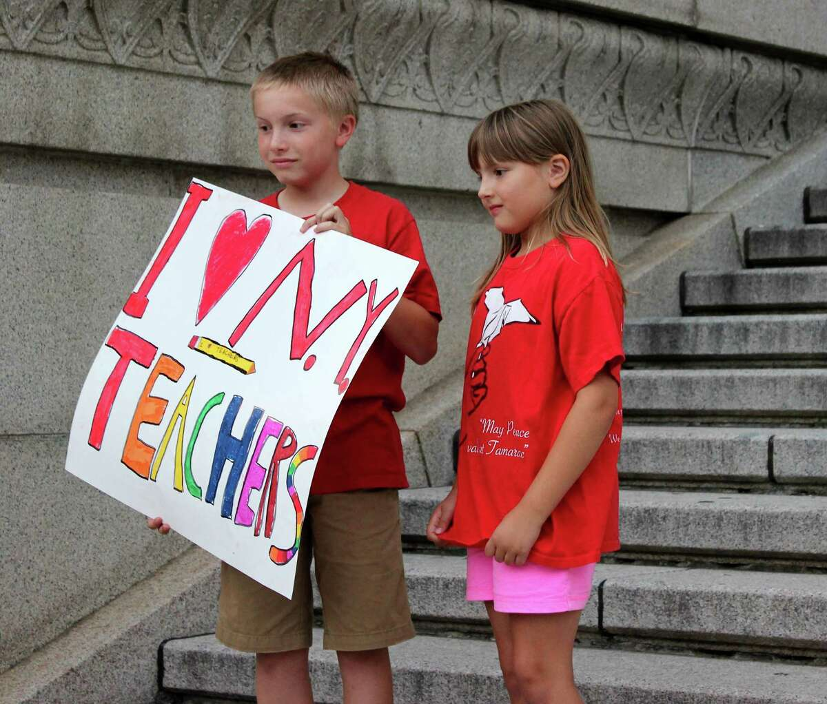 Eleven-year-old Michael Jacques, left, and 8-year-old Katelyn Jacques, right, of Waterford participate in the protests against the common core test contracts outside of the NYS Education Department on Monday evening, August 11, 2014, in Albany N.Y. (Selby Smith/Special to the Times Union)
