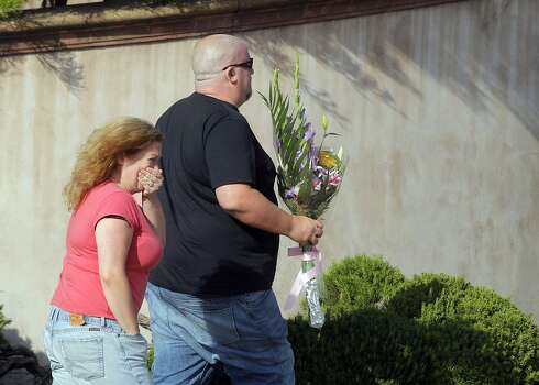 Alexis Cooney holds back tears as she and her brother, Nick Cooney, bring flowers to the Academy Award winner's former home in the Sea Cliff neighborhood of San Francisco. Photo: Carlos Avila Gonzalez, The Chronicle