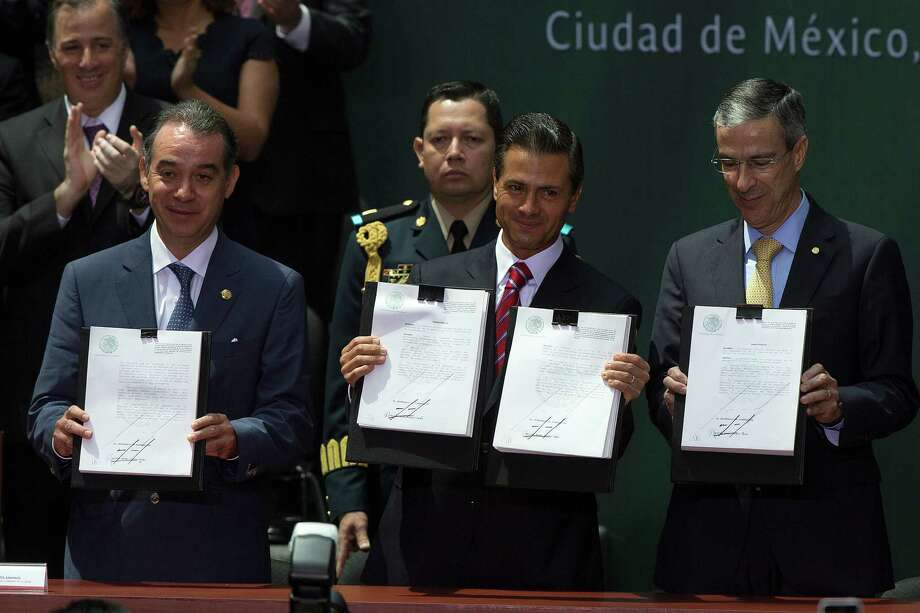 President Enrique Peña Nieto, center, displays legislation opening Mexico's energy industry to private investment. With him are Raul Cervantes Andrade, president of the Senate, left, and Jose Gonzalez Morfin, president of the Chamber of Deputies. Photo: Susana Gonzalez / © 2014 Bloomberg Finance LP