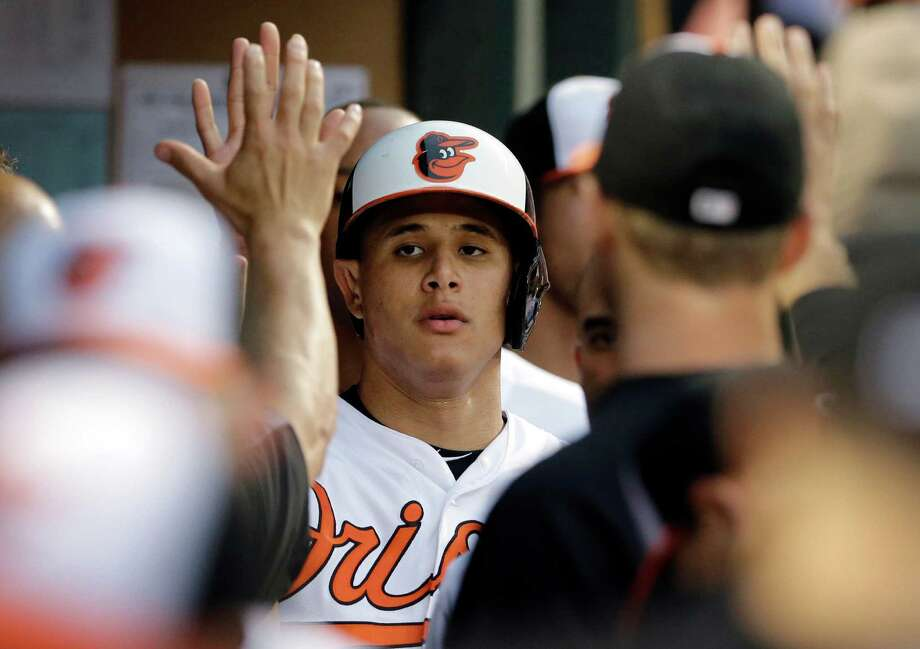 Baltimore Orioles' Manny Machado greets teammates in the dugout after scoring on a sacrifice fly ball by Nelson Cruz in the first inning of a baseball game against the New York Yankees, Monday, Aug. 11, 2014, in Baltimore. (AP Photo/Patrick Semansky) ORG XMIT: MDPS108 Photo: Patrick Semansky / AP