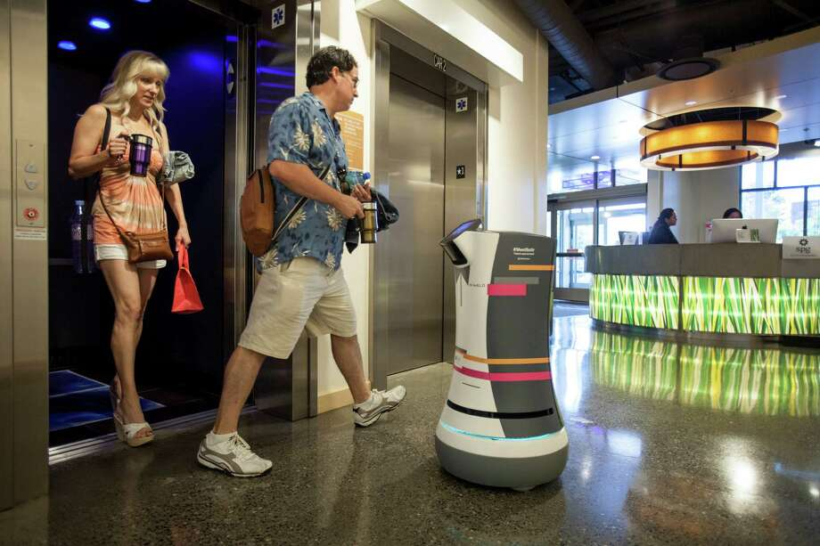 Botlr, a robotic bellhop that can deliver small items from the front desk to a client's room autonomously, waits for guests to leave an elevator at an Aloft hotel in Cupertino, Calif. Photo: PETER DASILVA, STR / NYTNS