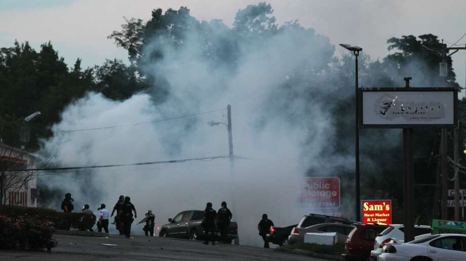Tactical officers fire tear gas on Monday, Aug. 11, 2014, in Ferguson, Mo. Authorities in Ferguson used tear gas and rubber bullets to try to disperse a large crowd Monday night that had gathered at the site of a burned-out convenience store damaged a night earlier, when many businesses in the area were looted.  Photo: Robert Cohen, AP / St. Louis Post-dispatch