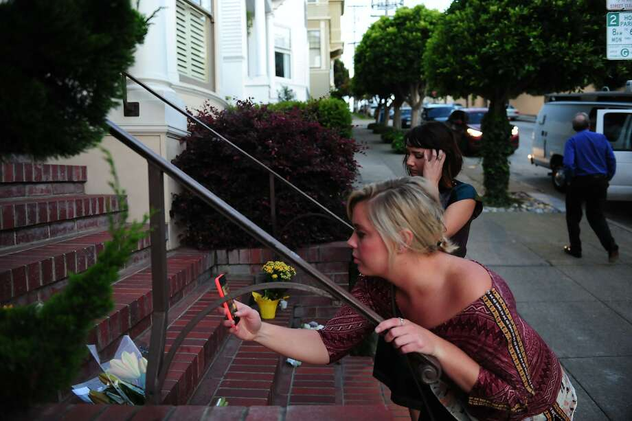 Samantha McMullen takes a photo of flowers as her friend Caitlin Kerton looks on outside the Mrs. Doubtfire house on August 11, 2014 in San Francisco, CA. Robin Williams was found dead this morning in his Tiburon home. Photo: Craig Hudson, The Chronicle