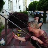 Samantha McMullen takes a photo of flowers as her friend Caitlin Kerton looks on outside the Mrs. Doubtfire house on August 11, 2014 in San Francisco, CA. Robin Williams was found dead this morning in his Tiburon home.