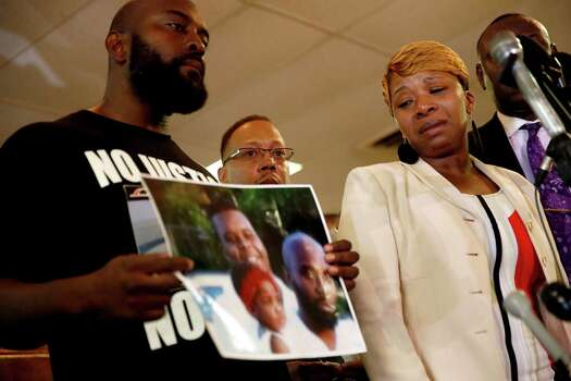 Lesley McSpadden, right, the mother of 18-year-old Michael Brown, watches as Brown's father, Michael Brown Sr., holds up a family picture of himself, his son, top left in photo, and a young child during a news conference Monday, Aug. 11, 2014, in Ferguson, Mo. Michael Brown, 18, was shot and killed in a confrontation with police in the St. Louis suburb of Ferguson, Mo, on Saturday, Aug. 9, 2014. Photo: Jeff Roberson, AP / AP