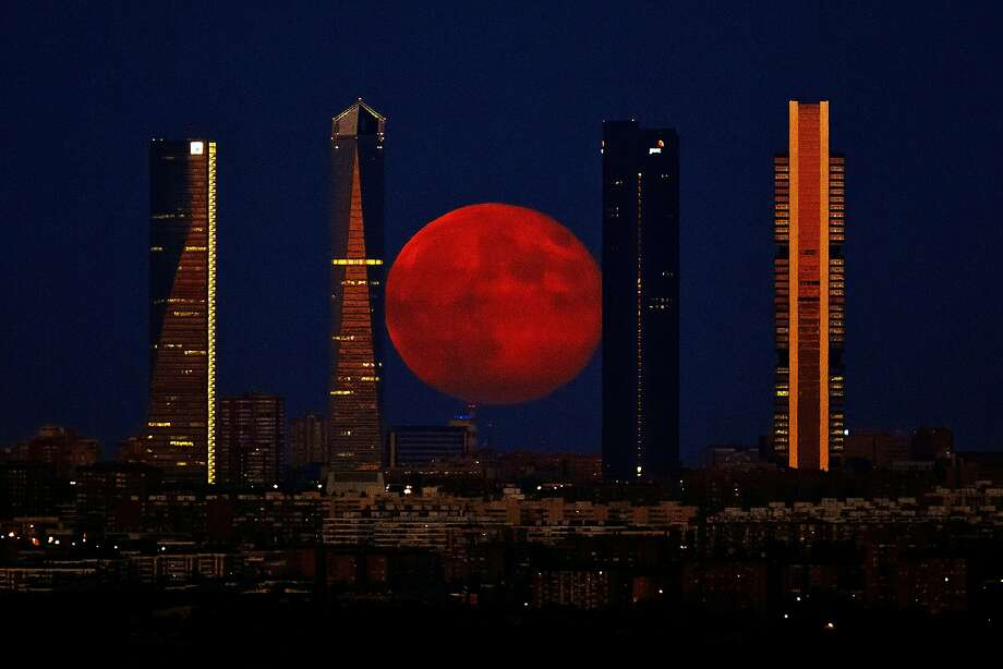 The moon rises in the sky as seen through the Four Towers or C.T.B.A. (Cuatro Torres Business Area), one of the main symbols of Madrid, Spain, Monday, Aug. 11, 2014. (AP Photo/Daniel Ochoa de Olza) Photo: Daniel Ochoa De Olza, Associated Press