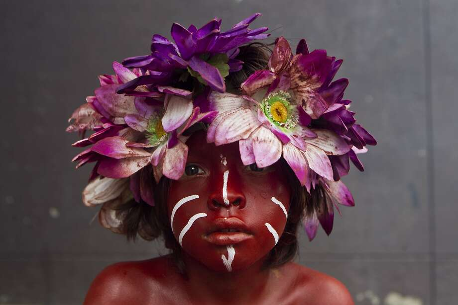 Flower child: A painted boy poses for a portrait during Santo Domingo festivities in Managua, Nicaragua. During the fests, Christians coat their bodies with used motor oil or red paint, and dress in traditional costumes to mark a miracle they believe was performed by Managua's patron saint, Santo Domingo de Guzman. Photo: Esteban Felix, Associated Press