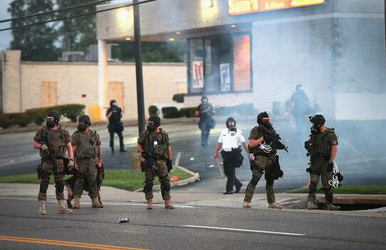 Tear gas hangs in the air as police force protestors from the business district into nearby neighborhoods on August 11, 2014 in Ferguson, Missouri. Police responded with tear gas and rubber bullets as residents and their supporters protested the shooting by police of an unarmed black teenager named Michael Brown who was killed Saturday in this suburban St. Louis community. Yesterday 32 arrests were made after protests turned into rioting and looting in Ferguson.  Photo: Scott Olson, Getty Images