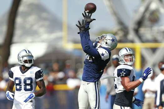 Dallas Cowboys cornerback Orlando Scandrick, middle, leaps to intercept a pass from Tony Romo, not pictured, in front of wide receiver Dez Bryant (88) and tight end Jason Witten, right, during the team's training camp on Sunday, Aug. 3, 2014, in Oxnard, Calif. (Ron Jenkins/Fort Worth Star-Telegram/MCT) Photo: Ron Jenkins, McClatchy-Tribune News Service / Fort Worth Star-Telegram
