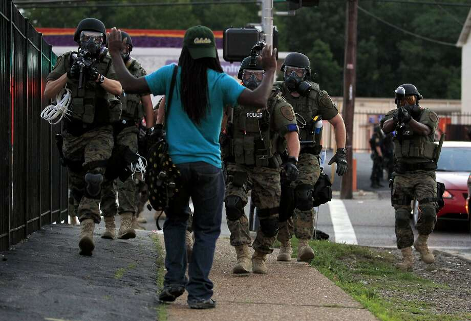 Police wearing riot gear walk toward a man with his hands raised Monday in Ferguson, Mo., site of nightly protests after Saturday's killing of Michael Brown. Photo: Jeff Roberson, Associated Press