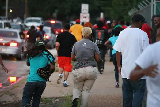 People flee as police advance on protestors firing tear gas and rubber bullets to force them from the business district into nearby neighborhoods on August 11, 2014 in Ferguson, Missouri. Residents and their supporters were protesting the shooting by police of an unarmed black teenager named Michael Brown who was killed Saturday in this suburban St. Louis community. Yesterday 32 arrests were made after protests turned into rioting and looting in Ferguson.  Photo: Scott Olson, Getty Images