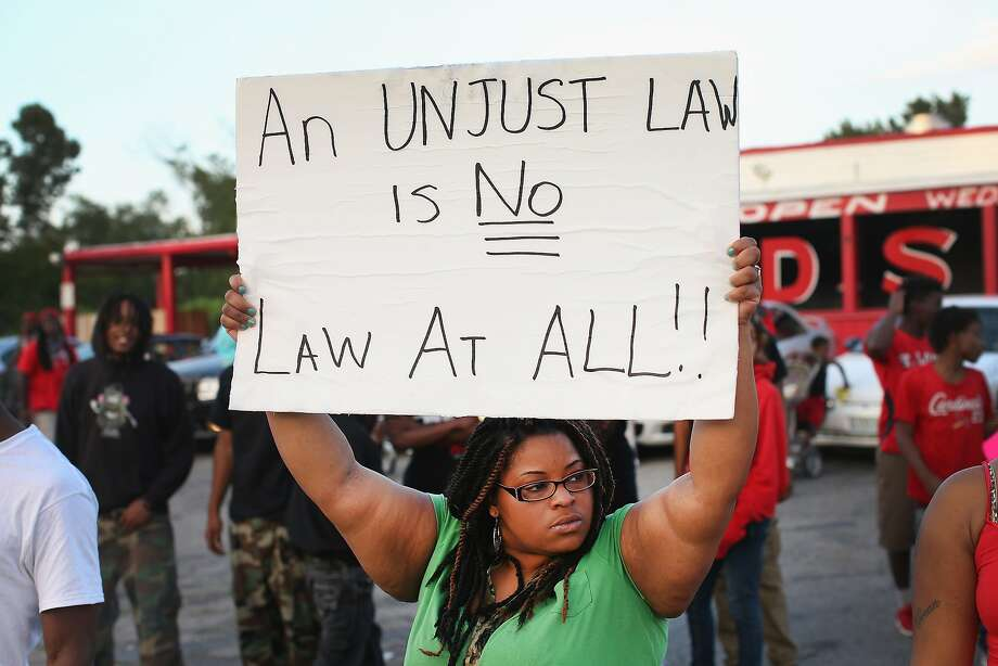 Demonstrators protest the killing of 18-year-old Michael Brown who was shot by police on Saturday on August 11, 2014 in Ferguson, Missouri. Police responded with tear gas and rubber bullets as residents and their supporters protested the shooting by police of an unarmed black teenager named Michael Brown who was killed Saturday in this suburban St. Louis community. Yesterday 32 arrests were made after protests turned into rioting and looting in Ferguson. Photo: Scott Olson, Getty Images