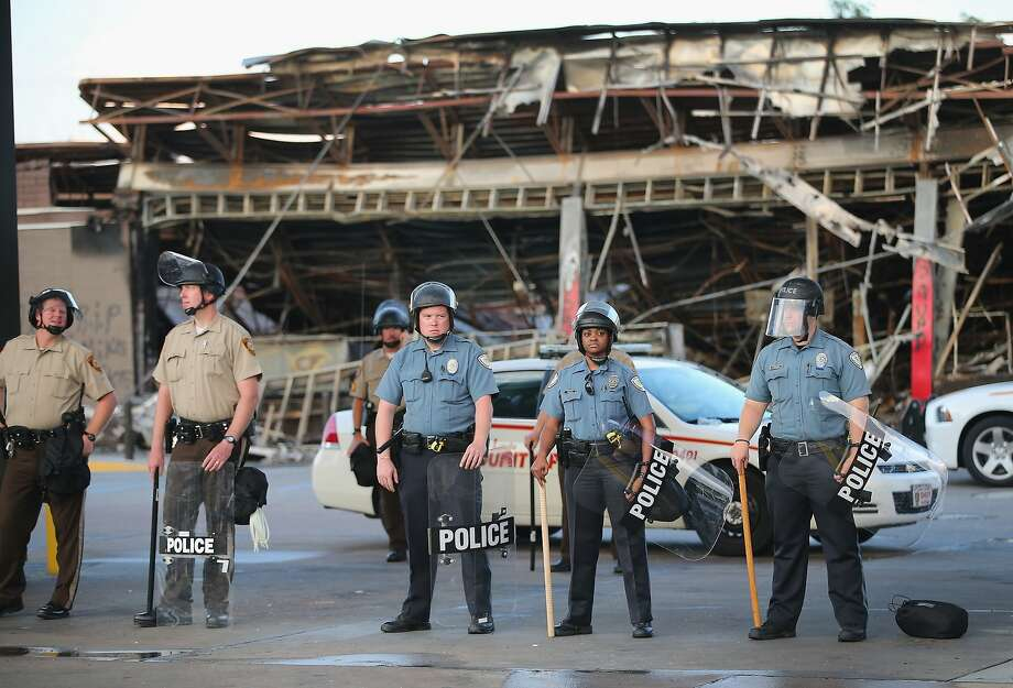 Police guard a Quick Trip gas station that was burned yesterday when protests over the killing of 18-year-old Michael Brown turned to riots and looting on August 11, 2014 in Ferguson, Missouri. Police responded with tear gas and rubber bullets as residents and their supporters protested the shooting by police of an unarmed black teenager named Michael Brown who was killed Saturday in this suburban St. Louis community. Yesterday 32 arrests were made after protests turned into rioting and looting in Ferguson.  Photo: Scott Olson, Getty Images