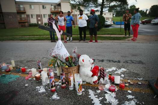 People view a memorial in the street where 18-year-old Michael Brown was shot by police on Saturday on August 11, 2014 in Ferguson, Missouri. Police responded with tear gas and rubber bullets as residents and their supporters protested the shooting by police of an unarmed black teenager named Michael Brown who was killed Saturday in this suburban St. Louis community. Yesterday 32 arrests were made after protests turned into rioting and looting in Ferguson.  Photo: Scott Olson, Getty Images