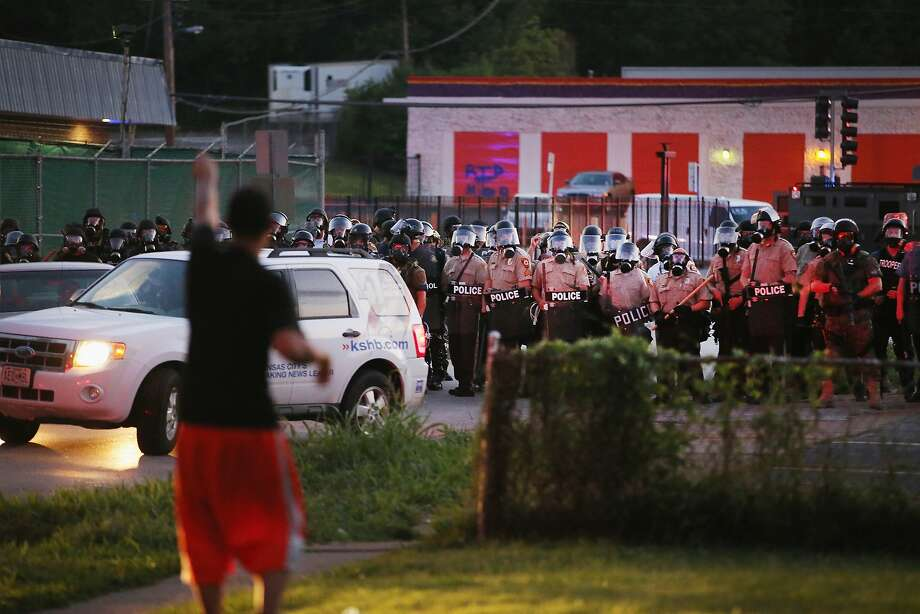 Police force protestors from the business district into nearby neighborhoods on August 11, 2014 in Ferguson, Missouri. Police responded with tear gas and rubber bullets as residents and their supporters protested the shooting by police of an unarmed black teenager named Michael Brown who was killed Saturday in this suburban St. Louis community. Yesterday 32 arrests were made after protests turned into rioting and looting in Ferguson. Photo: Scott Olson, Getty Images