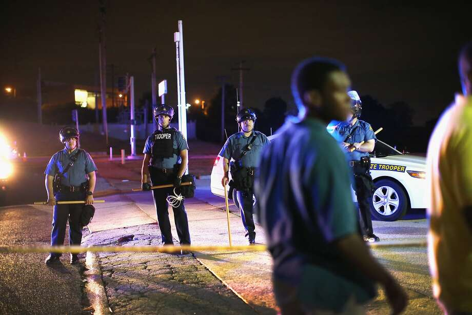 Police lock down a neighborhood on August 11, 2014 in Ferguson, Missouri. Police responded with tear gas as residents and their supporters protested the shooting by police of an unarmed black teenager named Michael Brown who was killed Saturday in this suburban St. Louis community. Yesterday 32 arrests were made after protests turned into rioting and looting in Ferguson.  Photo: Scott Olson, Getty Images