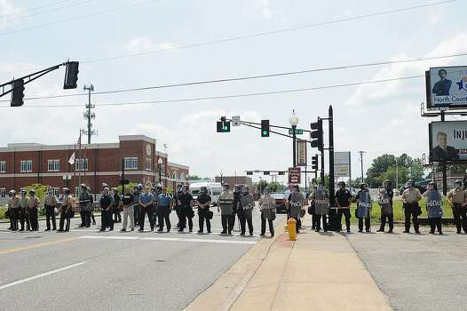 Police line up during a protest of the shooting death of 18-year-old Michael Brown outside Ferguson Police Department Headquarters August 11, 2014 in Ferguson, Missouri. The fatal shooting by police of the unarmed teen in Ferguson, Missouri has sparked outrage in the community and set off civil unrest including looting and vandalism.  Photo: Michael B. Thomas, Getty Images