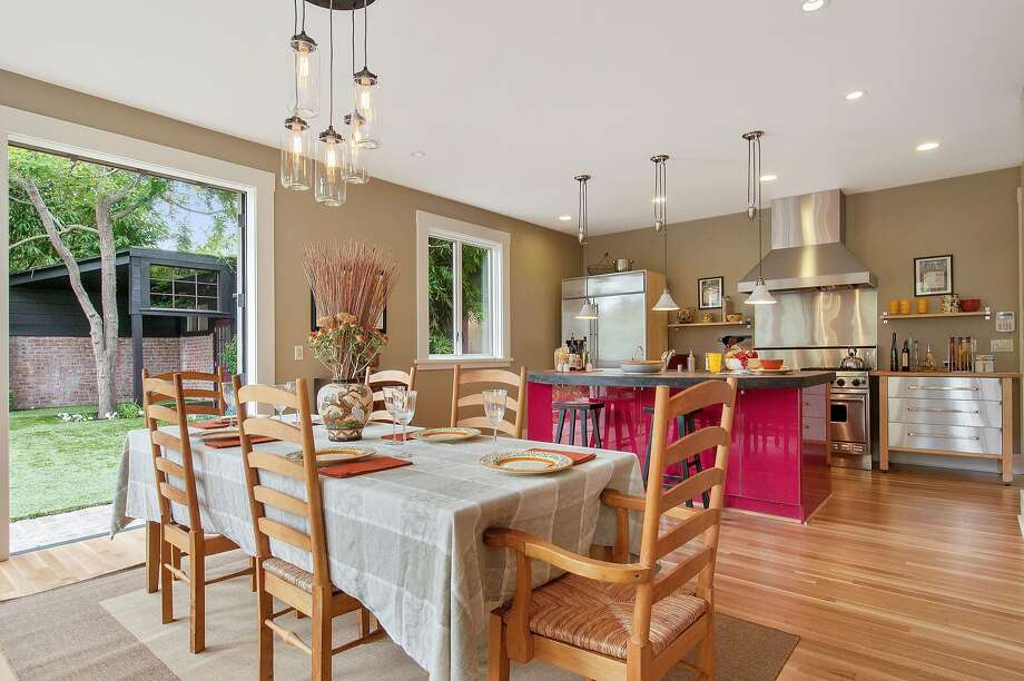 The eat-in kitchen has a vibrantly colored center island. Photo: Open Homes Photography
