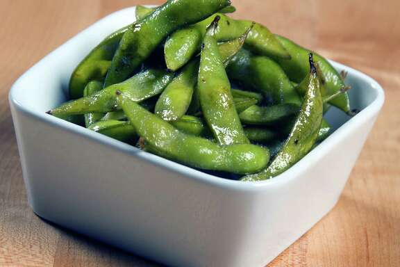 Eat edamame by putting the whole pod in your mouth, and then pull out the seeds with your teeth.