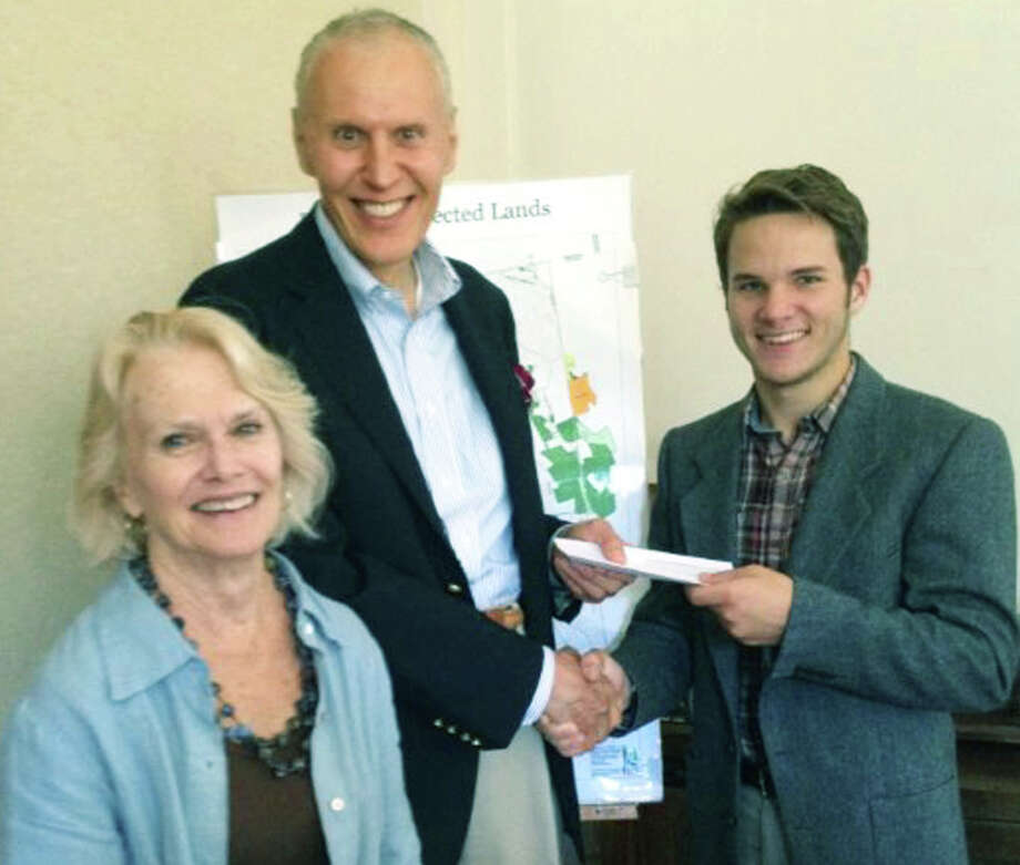 Recent Shepaug Valley School graduate Nate Steers, right, presents a donation of $500 from the sale of maple syrup for his Shepaug senior project to Steven Schinke, president of the Roxbury Land Trust, and Susan Payne, the trustâÄôs executive director.  Courtesy of Roxbury Land Trust Photo: Contributed Photo / The News-Times Contributed