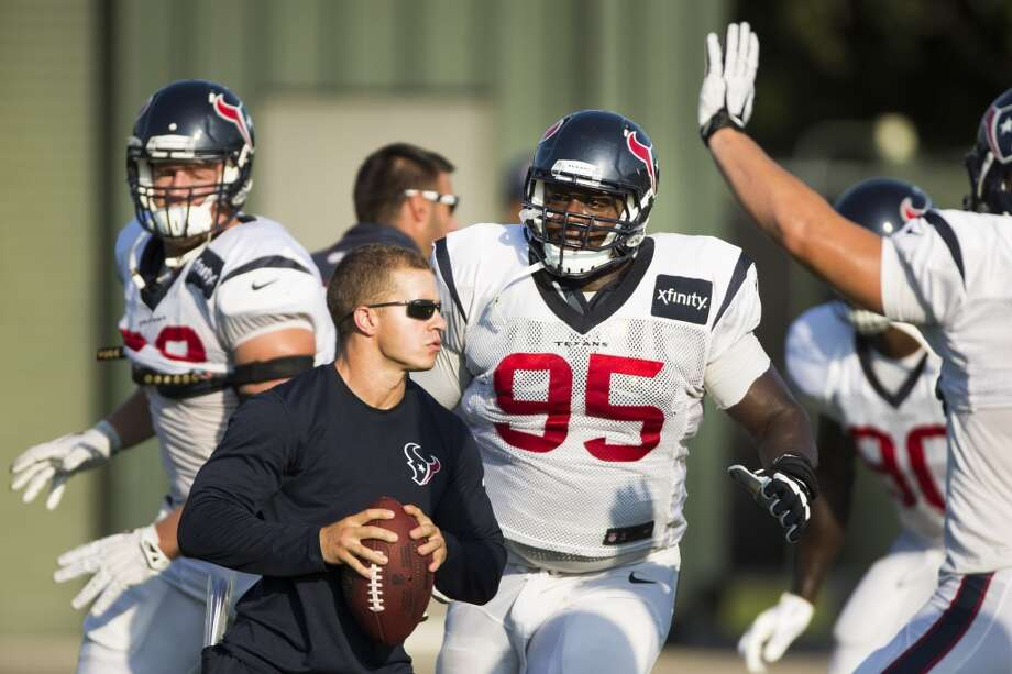 Defensive end J.J. Watt (99) and  nose tackle Jerrell Powe (95) run through a pass rush drill. Photo: Brett Coomer, Houston Chronicle