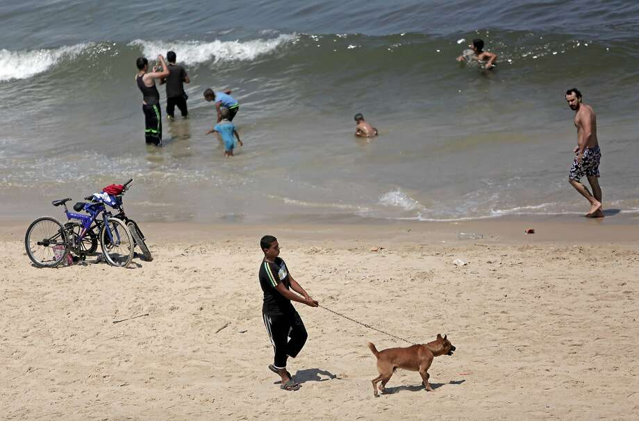 Palestinians swim on the beach in Gaza City on the second day of a three-day cease-fire. Photo: Khalil Hamra, Associated Press