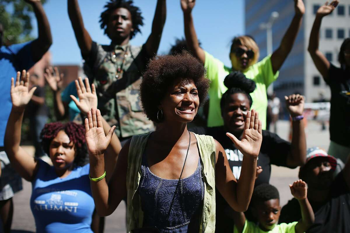 """CLAYTON, MO - AUGUST 12: Demonstrators raise their hands and chant """"hands up, don't shoot"""" during a protest over the killing of Michael Brown on August 12, 2014 in Clayton, Missouri. Some reports state that Brown hand his hands in the air when he was shot and killed by a police officer on Saturday in suburban Ferguson, Missouri. Two days of unrest including rioting and looting have followed the shooting in Ferguson. Browns parents have publicly asked for order. (Photo by Scott Olson/Getty Images)"""