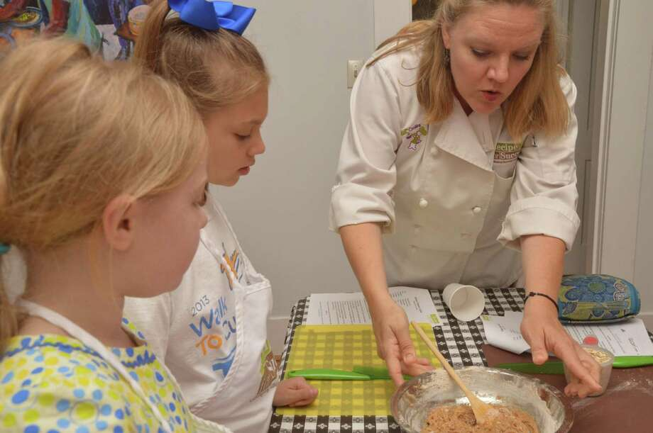 Susie Mullen, culinary education coordinator at Recipe House in Montrose, helps Brenna Kallesen, Friendswood, and Nicole McGill, 10, of Friendswood with healthy recipes. Photo: Jimmy Loyd / freelance