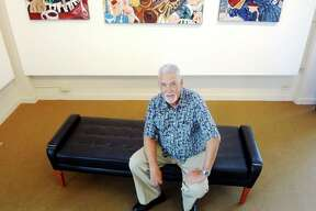 Smith sits among his works at the Carver Community Cultural Center, where his exhibit runs through Aug. 26.