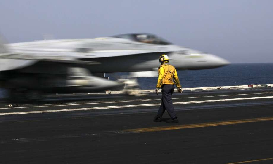 Jihadists targeted: An F/A-18 fighter jet takes off for Iraq from the flight deck of the carrier USS George H.W. Bush in the Persian Gulf. U.S. military officials said American fighters attacked an Islamic State group convoy moving against Kurdish forces defending the northeastern Iraqi city of Irbil. Photo: Hasan Jamali, Associated Press