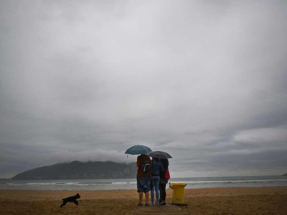 The rain in Spain:A dog runs on the beach during a shower in Laredo, northern Spain. Photo: Alvaro Barrientos, Associated Press