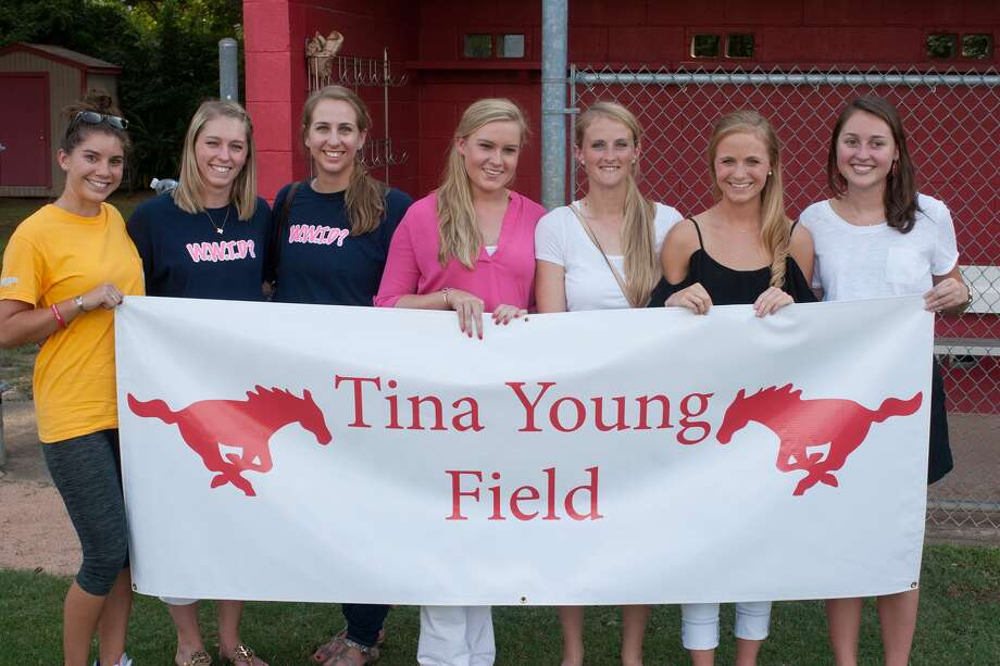 Several former student-athletes display a banner dedicating the Memorial High School softball field to former coach Tina Young.  From left are Anna Vazquez, Brittany Chaney, Erin Rudd, Taylor Stewart, Leslie LeJune, Mackenzie Meador and Blanche Schwabenland. Several former student-athletes display a banner dedicating the Memorial High School softball field to former coach Tina Young.  From left are Anna Vazquez, Brittany Chaney, Erin Rudd, Taylor Stewart, Leslie LeJune, Mackenzie Meador and Blanche Schwabenland. Photo: R. Clayton McKee, Freelance / © R. Clayton McKee
