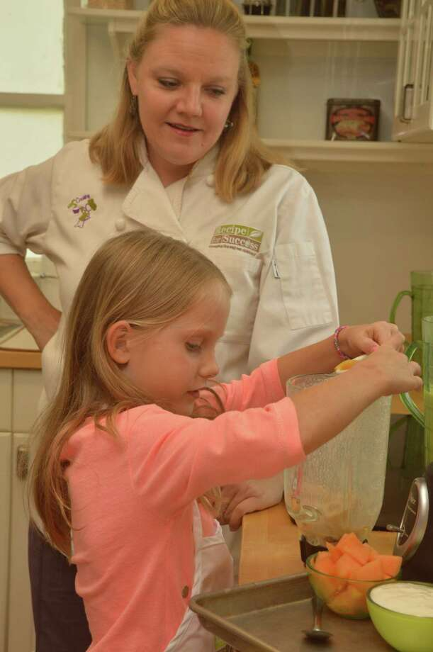 Susie Mullen, culinary education coordinator at Recipe House, helps Girl Scout Caris Lauritsen, 9, of Memorial, make smoothies.Susie Mullen, culinary education coordinator at Recipe House, helps Girl Scout Caris Lauritsen, 9, of Memorial, make smoothies. Photo: Jimmy Loyd / freelance