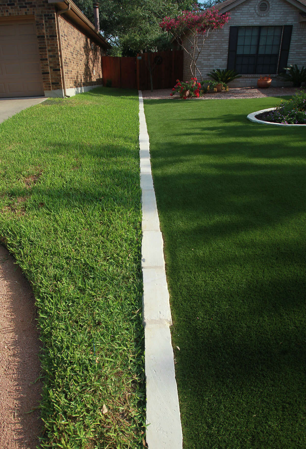 A limestone divider separates Bill Fenstermacher's artificial lawn (right) from his neighbor's St. Augustine lawn (left). Fenstermacher's homeowner association in Villages of Westcreek approves synthetic grass because of water savings.