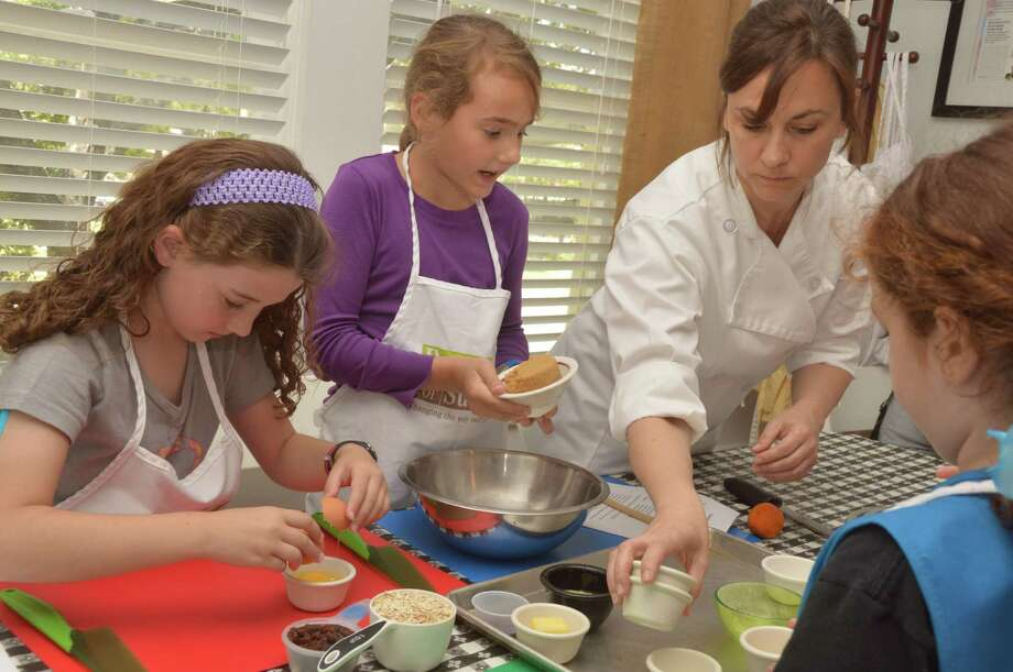 Girl Scouts Savannah Richard, 10, of Houston; Ella Hill, 10, of Katy; and Mickey Holden, 10, of Katy learn from nutrition instructor Sandra Mangini how to make healthy meals.Girl Scouts Savannah Richard, 10, of Houston; Ella Hill, 10, of Katy; and Mickey Holden, 10, of Katy learn from nutrition instructor Sandra Mangini how to make healthy meals.Girl Scouts Savannah Richard, 10, of Houston; Ella Hill, 10, of Katy; and Mickey Holden, 10, of Katy learn from nutrition instructor Sandra Mangini how to make healthy meals. Photo: Jimmy Loyd / freelance