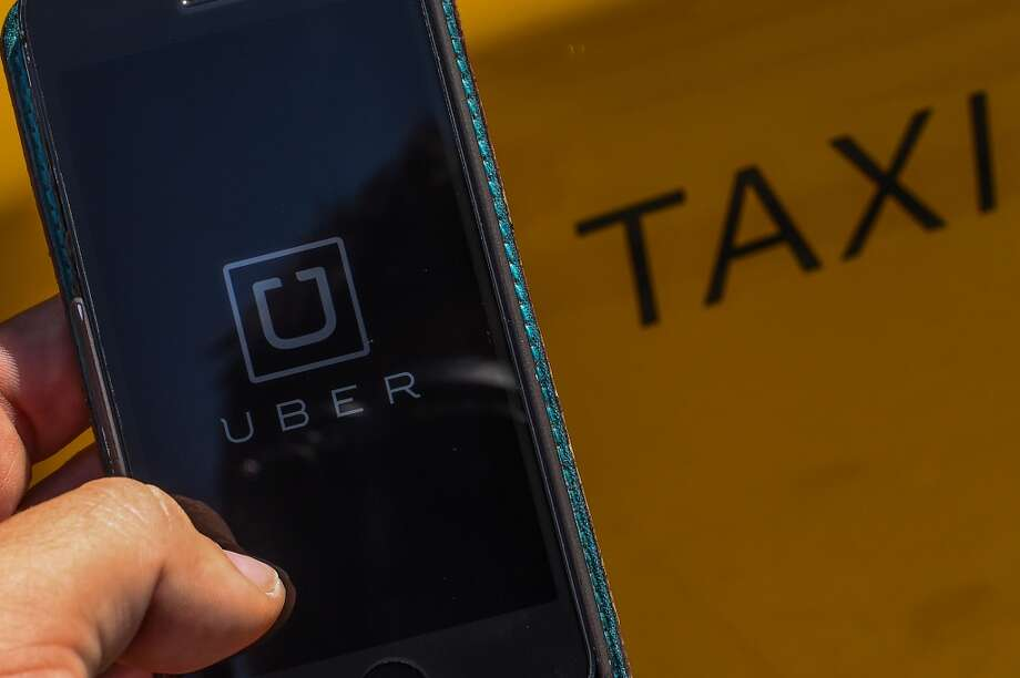 In this photo illustration, the new smart phone app 'Uber' logo is displayed on a mobile phone next to a taxi on July 1, 2014 in Barcelona, Spain.(Photo Illustration by David Ramos/Getty Images) Photo: David Ramos, Getty Images