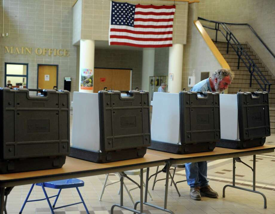 Dennis Welsh votes in the primary election Tuesday, Aug. 12, 2014 at Shelton Intermediate School in Shelton, Conn. Turnout is fairly low for the district with just 233 votes cast at 4:45 pm. Photo: Autumn Driscoll / Connecticut Post