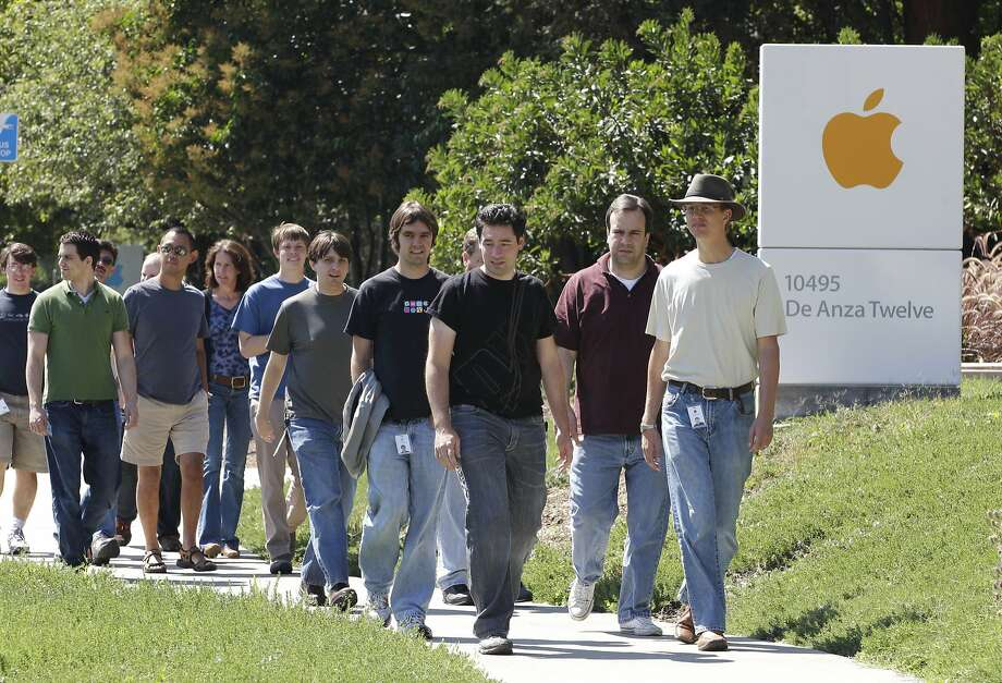 Apple workers walk between buildings at the Cupertino headquarters. The majority of employees at the tech company are men. Photo: Paul Sakuma, Associated Press