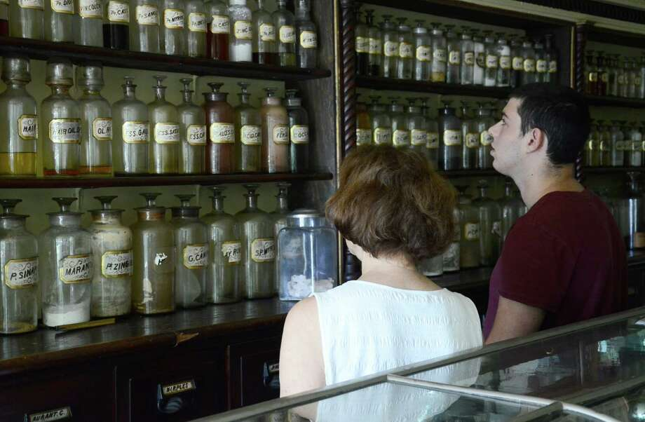 New Canaan Historical Society's Executive Director Janet Lindstrom gives a tour of the Cody Drug Store model to Andrew Schwartz in New Canaan, Conn., on Friday, Aug. 8, 2014. Schwartz recently found an early 1900s' medicine bottle from the pharmacy while exploring the woods of North Stamford with a metal detector. Photo: Nelson Oliveira / New Canaan News